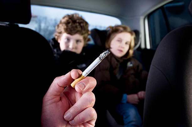 Young Children Suffering The Effects of In Car Passive Smoking Two young children being subjected to the effects of passive smoking from their mother's cigarette. smoking issues stock pictures, royalty-free photos & images