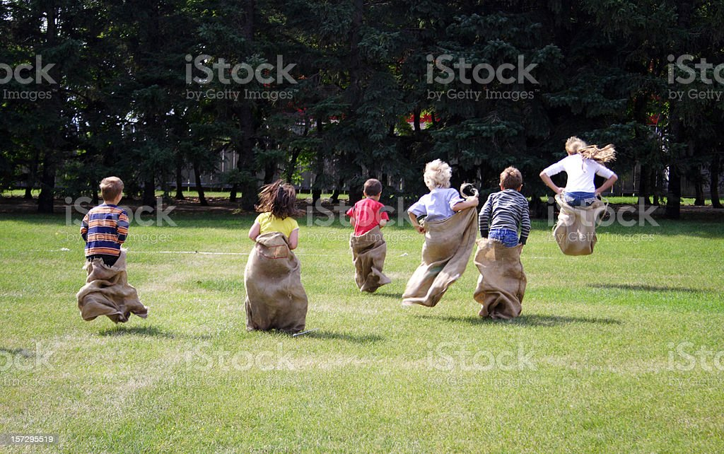 Young children taking part in a sack race stock photo
