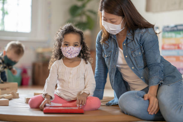 Young children wearing face masks at daycare stock photo