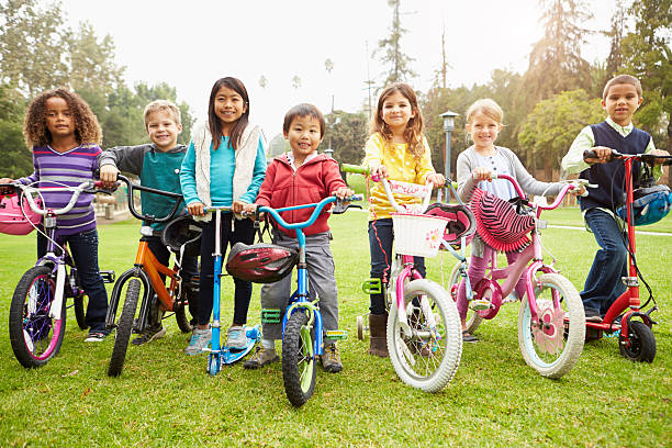Young Children With Bikes And Scooters In Park stock photo