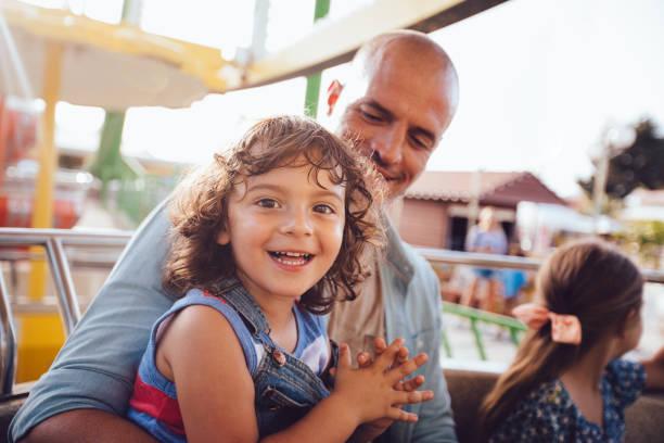 Paseo de los niños con el padre en el parque de atracciones de la rueda de la fortuna - foto de stock