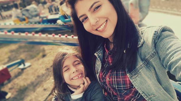 Passeio das crianças jovens com a mãe na roda gigante de parque de diversões - foto de acervo