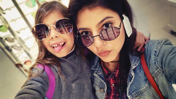 Crianças com a mãe na tentativa de óculos de sol - foto de acervo