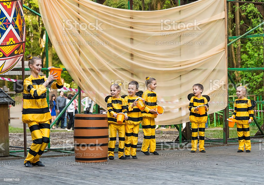 Young children with the teacher on stage in costume bee stock photo