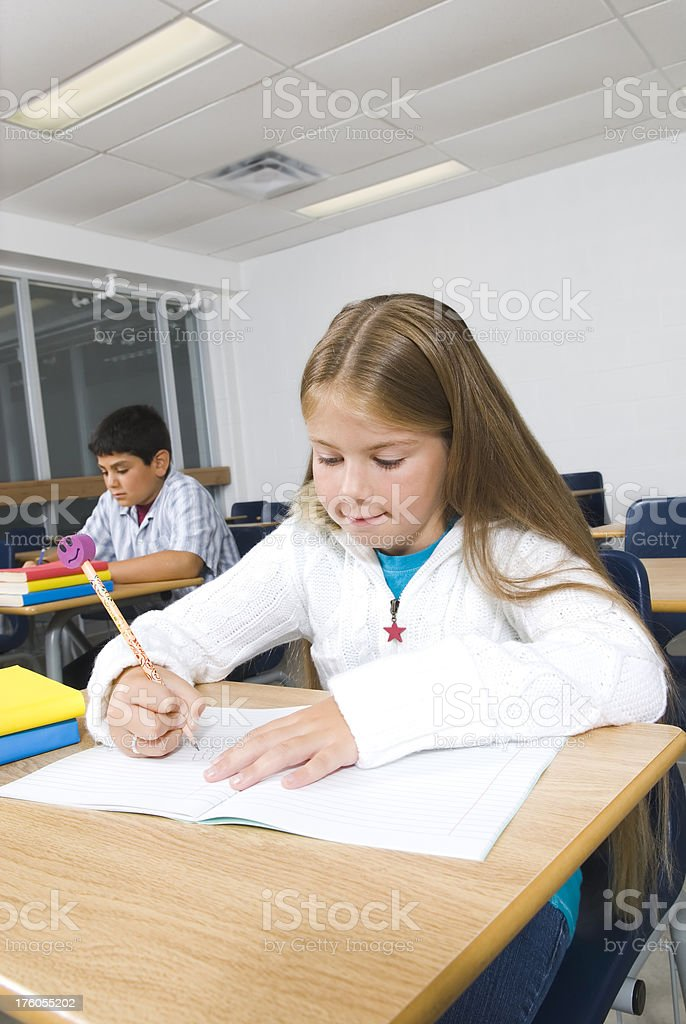 Young children writing in the primary school classroom - I royalty-free stock photo