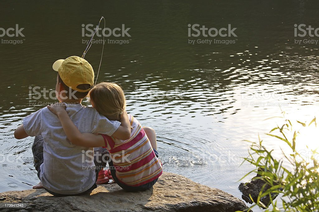 Young children/friends sitting at the pond/lake stock photo