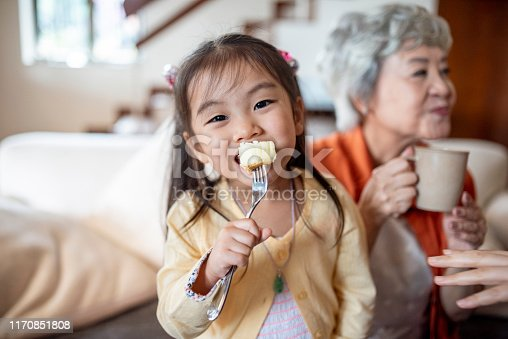 Cheerful Chinese girl enjoying big bite of sponge cake for her birthday with grandmother in background.
