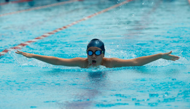 Young chinese boy with goggles swims butterfly stock photo