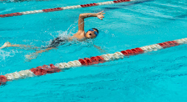 Young chinese boy with goggles swims freestyle stock photo