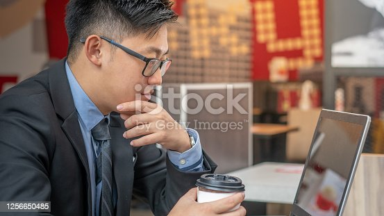 Side view of Chinese ethnicity stockbroker monitoring the stock market before proposal the stock's value and trading activity to his client. He holding a cup of coffee and using the laptop in the cafe shop.