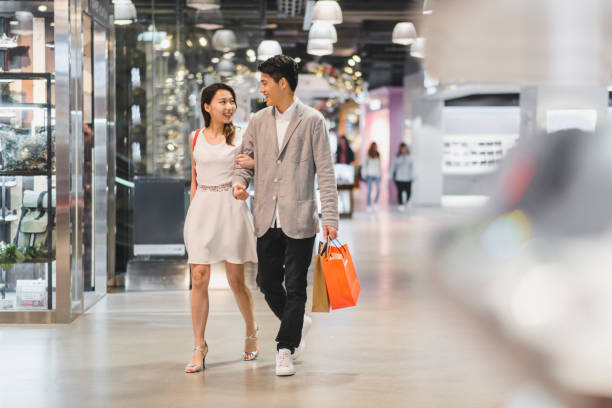 Young Chinese couple in the shopping centre Young Chinese couple in the shopping centre shopping couple asian stock pictures, royalty-free photos & images