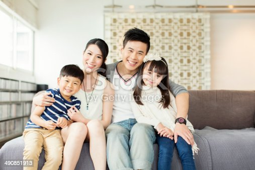 Portrait of a young Chinese family in their Hong Kong apartment.