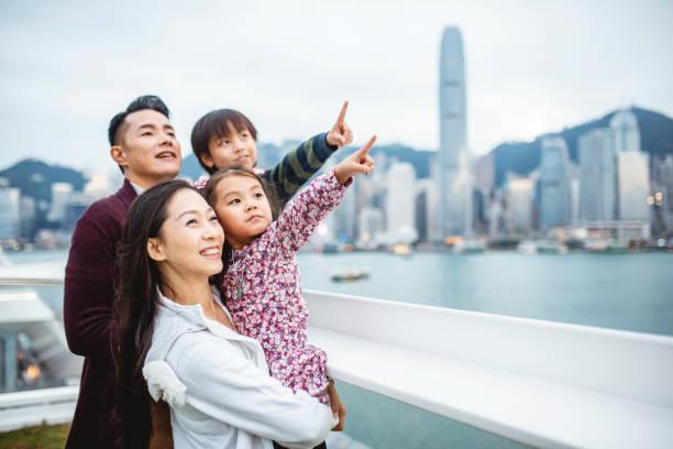 Junge chinesische Familie zeigt auf Hong Views von Deck – Foto