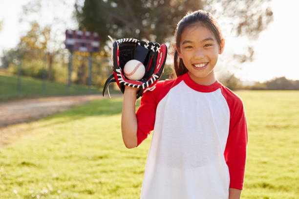 Young Chinese girl holding baseball in mitt looks to camera Young Chinese girl holding baseball in mitt looks to camera baseball sport stock pictures, royalty-free photos & images