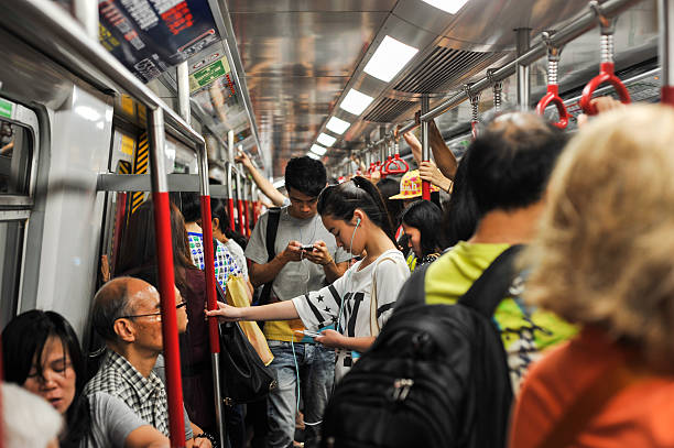 Young chinese girl looking at her smartphone in the train stock photo
