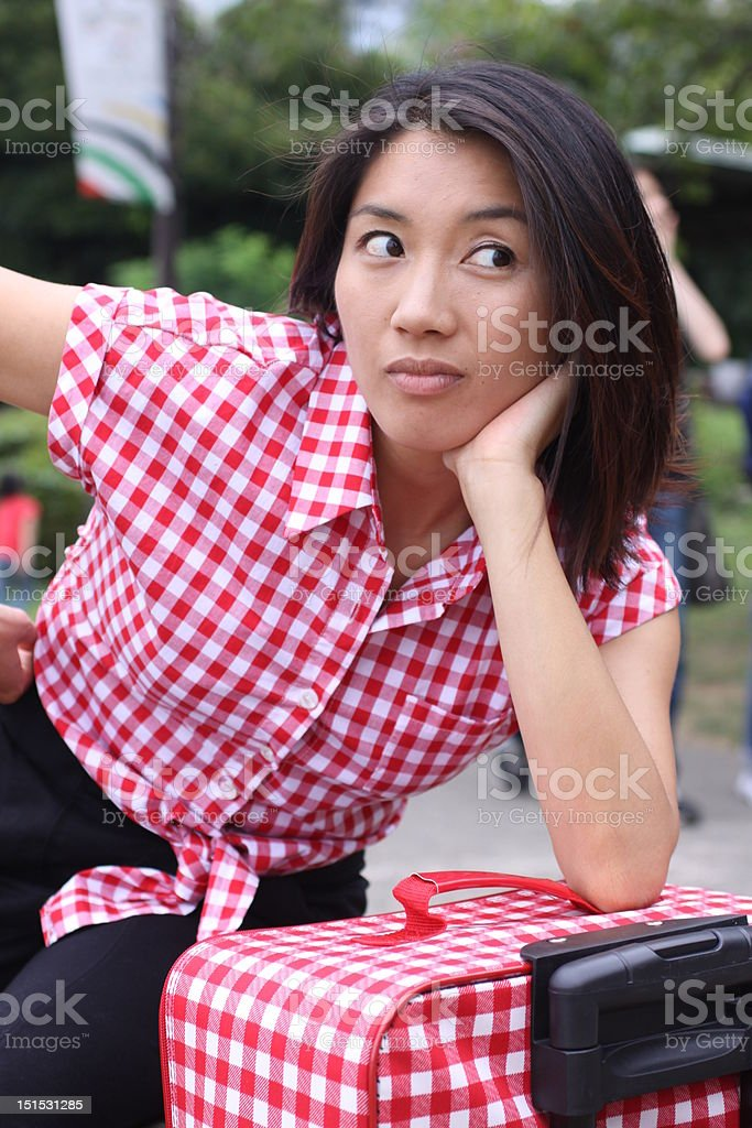 Young Chinese girl on a suitcase getting bored stock photo