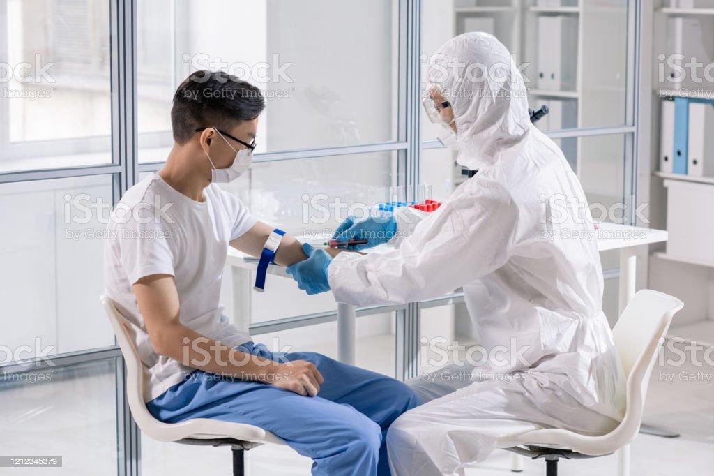 Junger Chinesischer Mann in Maske sitzt im Labor, während Arzt nahm sein Blut - Lizenzfrei Arbeiten Stock-Foto