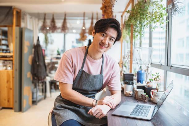 Junger Chinese mit Laptop und Arbeit in einem Töpfergeschäft – Foto