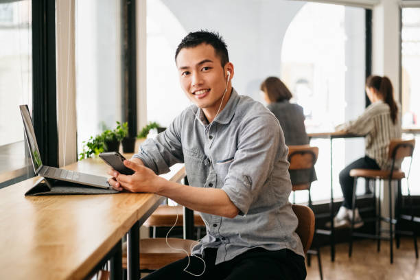Young Chinese man wearing earphones with smartphone and laptop in office stock photo