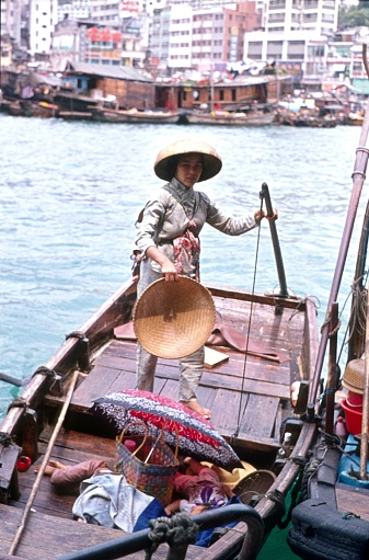 Hong Kong, China, 1974. Young Chinese mother with her sleeping children on a boat in front of Hong Kong.