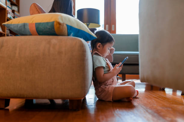 gadis muda prasekolah cina bermain game di ponsel pintar - child playing phone potret stok, foto, & gambar bebas royalti