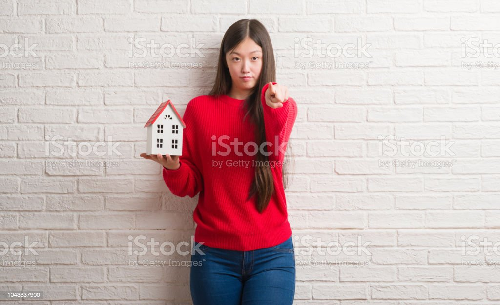 Young Chinese real state agent woman over brick wall holding house...