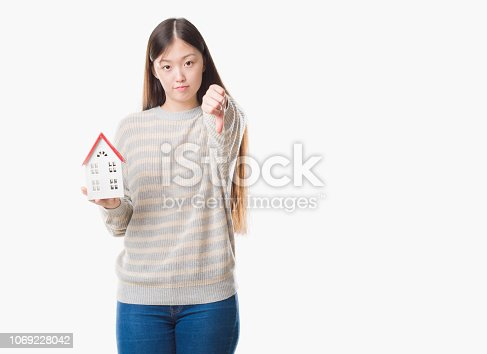 Young Chinese real state agent woman over isolated background holding house with angry face, negative sign showing dislike with thumbs down, rejection concept