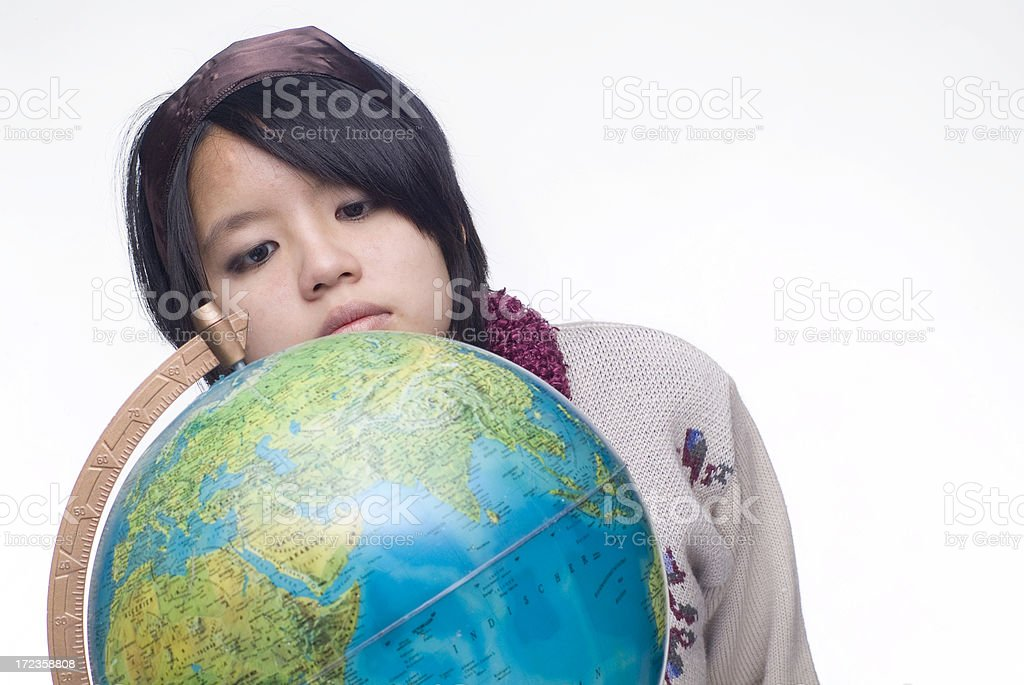 Young Chinese woman looking with interest at a globe royalty-free stock photo