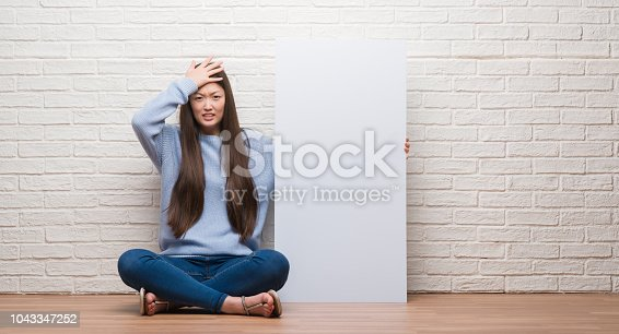 istock Young Chinese woman over brick wall holding banner stressed with hand on head, shocked with shame and surprise face, angry and frustrated. Fear and upset for mistake. 1043347252