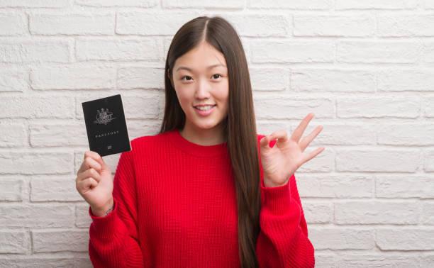Young chinese woman over brick wall holding passport of australia ok picture id1042457104?b=1&k=6&m=1042457104&s=612x612&w=0&h=sjey7pwjreipgptnki2gdyxpnr7gg6a7jijx7fguupq=