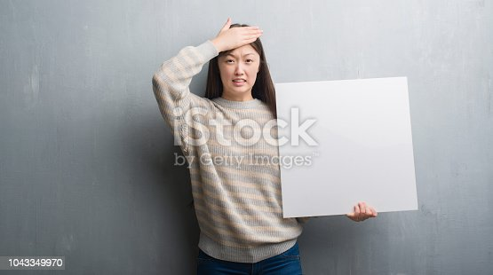 istock Young Chinese woman over grey wall holding banner stressed with hand on head, shocked with shame and surprise face, angry and frustrated. Fear and upset for mistake. 1043349970