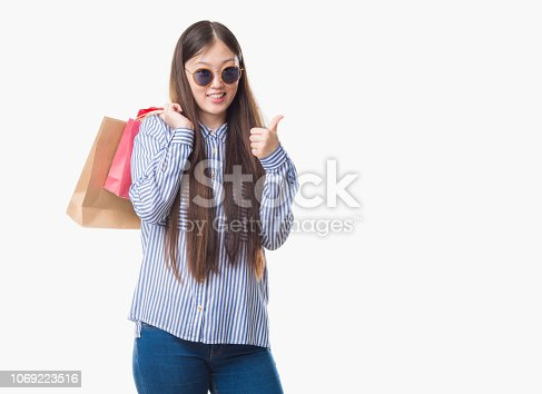Young Chinese woman over isolated background holding shopping bags on sales happy with big smile doing ok sign, thumb up with fingers, excellent sign