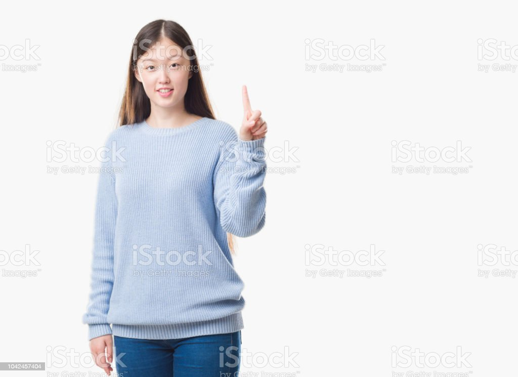 Young Chinese woman over isolated background showing and pointing up with finger number one while smiling confident and happy. stock photo