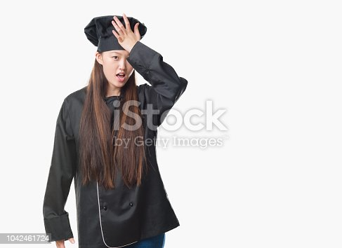 1046559700istockphoto Young Chinese woman over isolated background wearing chef uniform surprised with hand on head for mistake, remember error. Forgot, bad memory concept. 1042461724