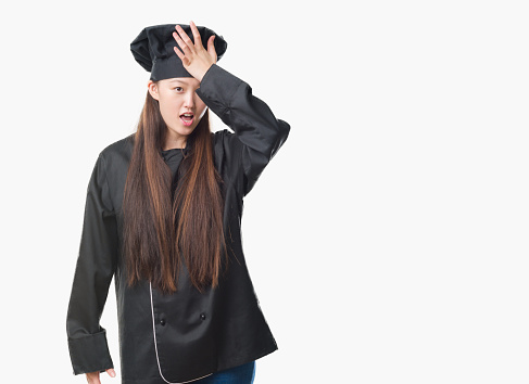 1046559700 istock photo Young Chinese woman over isolated background wearing chef uniform surprised with hand on head for mistake, remember error. Forgot, bad memory concept. 1042461724