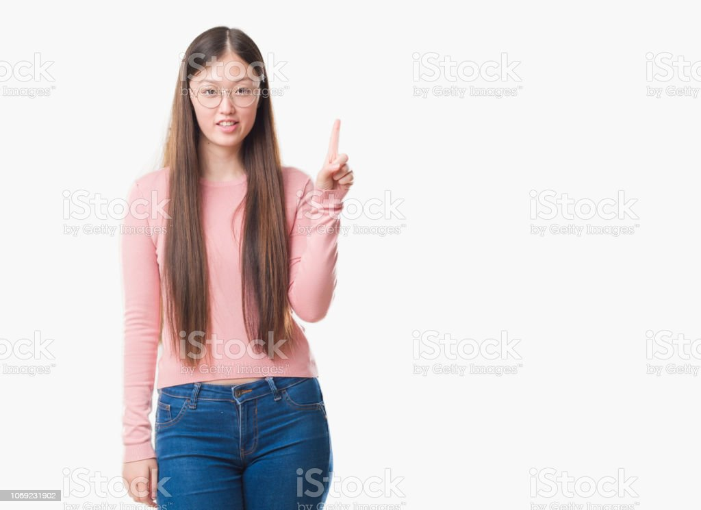Young Chinese woman over isolated background wearing glasses showing and pointing up with finger number one while smiling confident and happy. stock photo