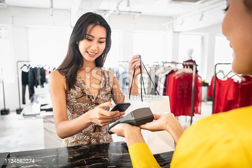 istock Young Chinese woman paying with phone in boutique 1134562274