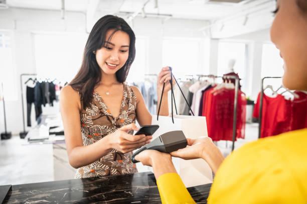 Junge Chinesin zahlt mit Telefon in Boutique – Foto
