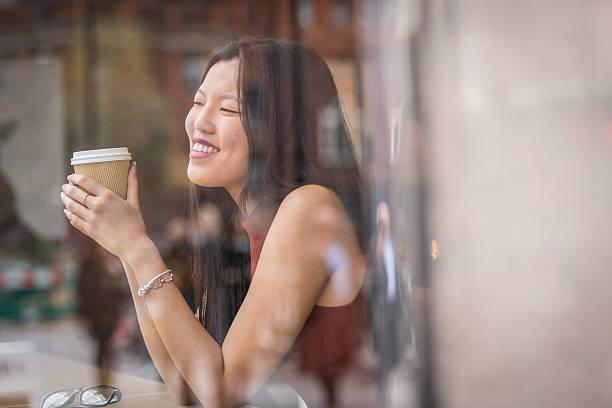 Junge chinesische Frau sitzt neben Fenster im Café. – Foto
