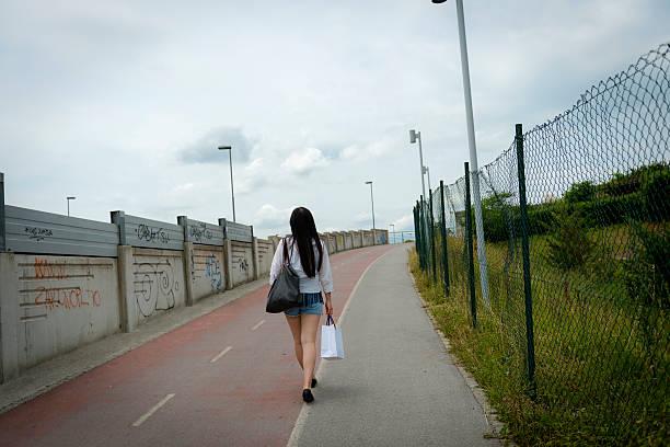 junge chinesische frau zu fuß auf radweg nach dem einkaufsbummel - maschendrahtzaun preis stock-fotos und bilder