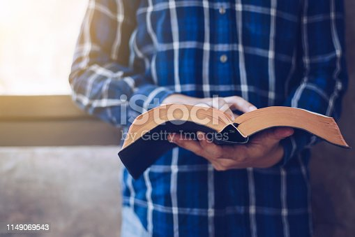 Close up of Young christian man standing at concrete wall while read bible with window light