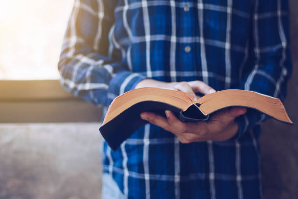 Young Christian man reading bible Close up of Young christian man standing at concrete wall while read bible with window light place of worship stock pictures, royalty-free photos & images