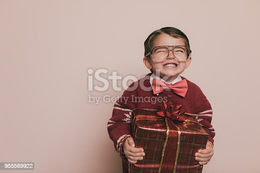 Young Christmas sweater boy with eyeglasses and an ugly sweater is laughing at the camera. He loves getting presents from Santa at Christmas. He enjoys the excitement and happiness that comes with the holidays.