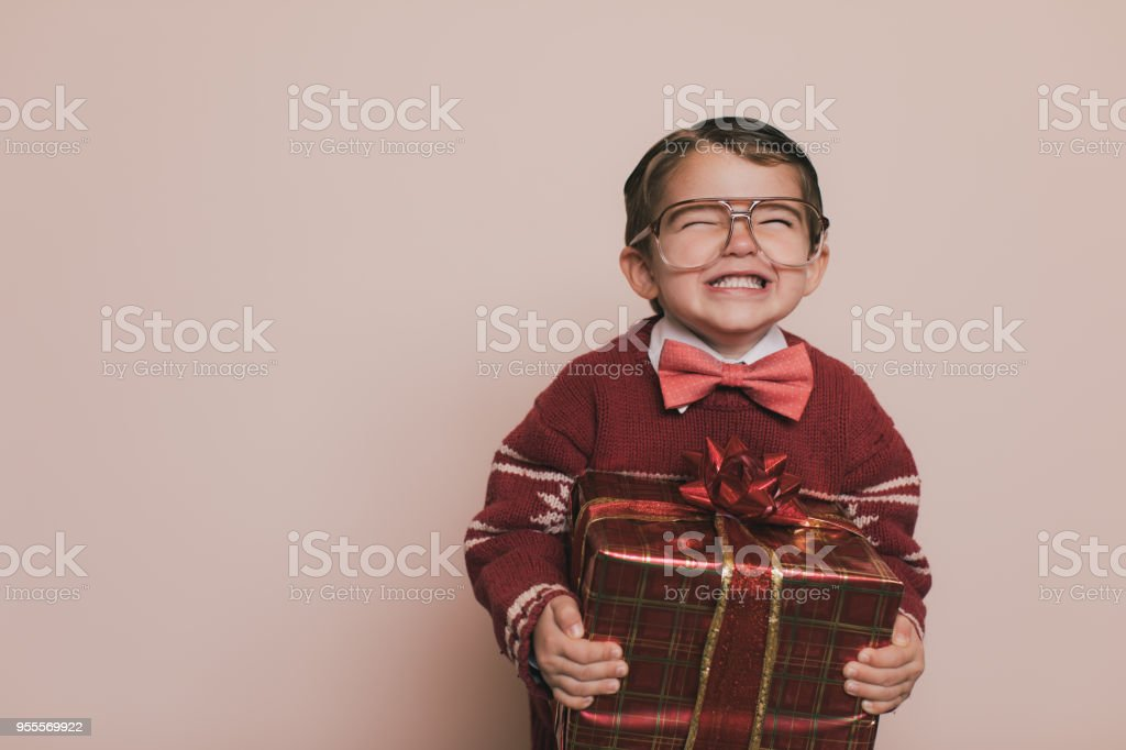 Young Christmas Sweater Boy Smiles with Gift stock photo