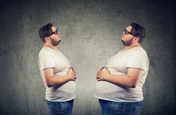 young chubby man looking at fat himself feeling bloated. - metabolic syndrome stock photos and pictures