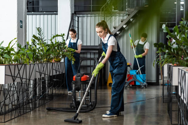 young cleaner vacuuming floor in office near colleagues stock photo