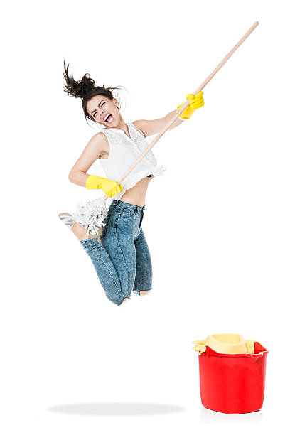 young cleaning housewife jumping and playing guitar with the broom - household chores stock photos and pictures