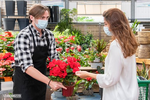 Young clerk wearing an apron and a surgical mask showing a beautiful plant to a young woman on an out of focus background. Garden center and shopping concept.