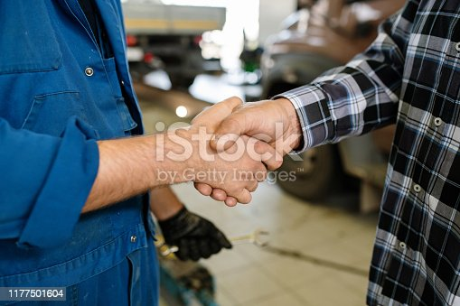 Young client of contemporary car repair service and professional technician greeting one another by handshake
