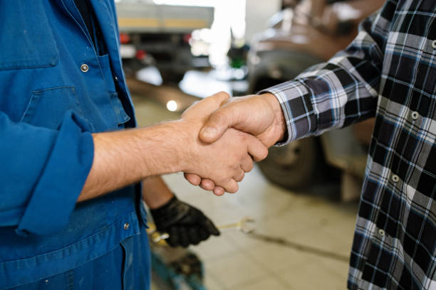 Young client of repair service and technician greeting one another by handshake stock photo